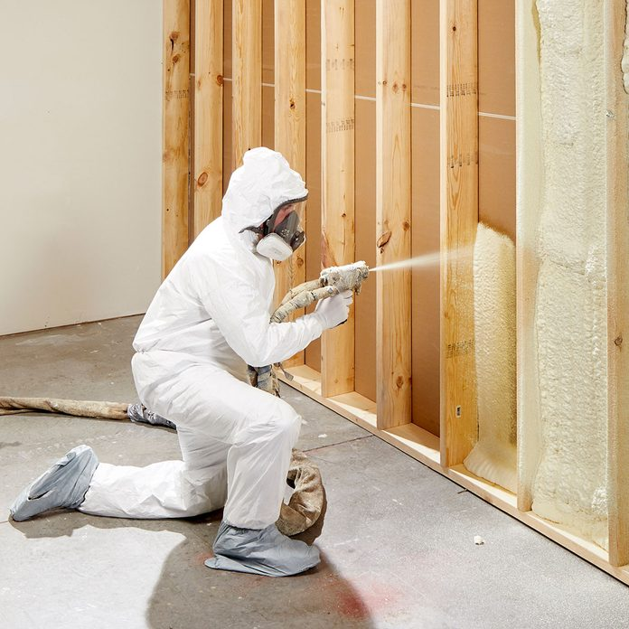A man in a protective suit spraying insulation between rafters